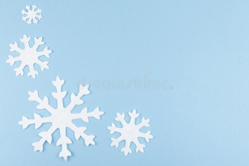 Christmas or New Year composition made of felt snowflakes on blue background. Winter season backdrop with decorative toys, minimal stock images
