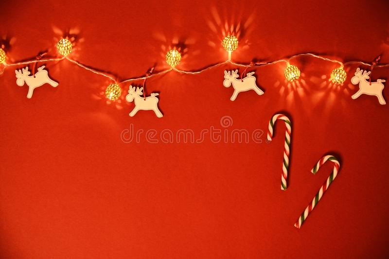Christmas and New Year composition. Seasonal greeting card concept with white Christmas lights, reindeers and candy cane on red. Background. Christmas, winter royalty free stock image
