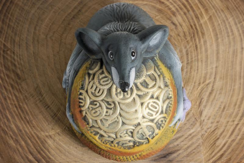 Christmas or New Year composition. The symbol of 2020 is a gray rat with coins on a wooden table . Top view.  royalty free stock photography