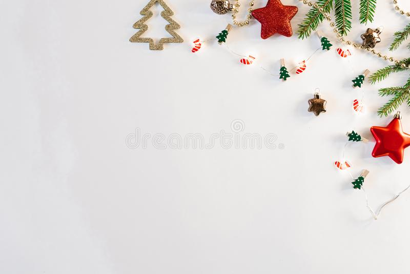 Christmas and new year composition. Christmas toys, lights or garland and spruce branches on a white background. Flat layer, top v. Iew, space to copy text stock photo