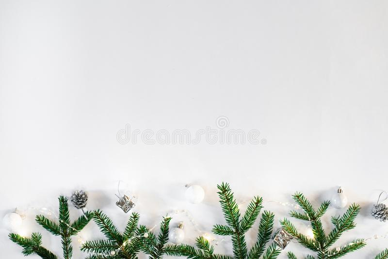 Christmas and new year composition. Christmas toys, lights or garland and spruce branches on a white background. Flat layer, top v. Iew, space to copy text royalty free stock image