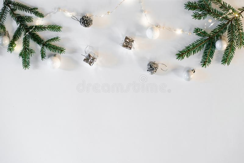 Christmas and new year composition. Christmas toys, lights or garland and spruce branches on a white background. Flat layer, top v. Iew, space to copy text stock image