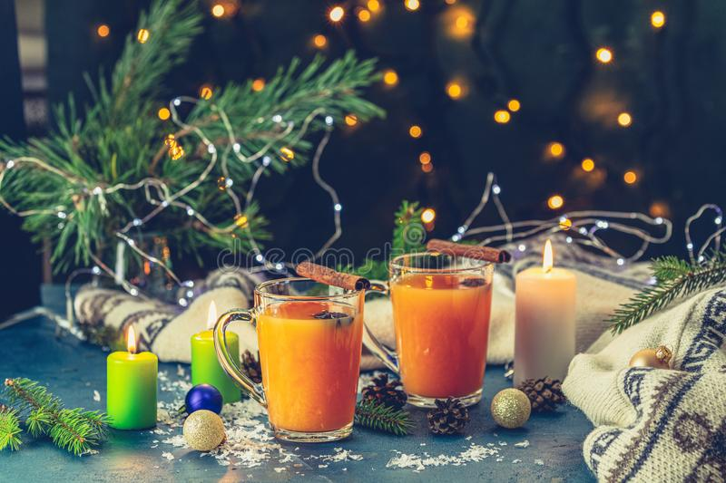 Christmas and New Year composition. Two cup of hot spicy tea with sea buckthorn, cinnamon and star anise, branches of pine and. Spruce, candles and holiday royalty free stock images
