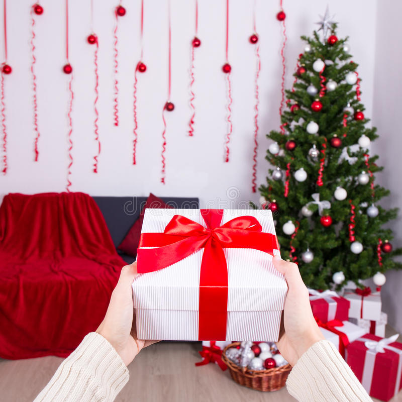 Christmas and new year concept - gift box in male hand in decorated interior. Christmas and new year concept - gift box in male hand in decorated living room stock photos