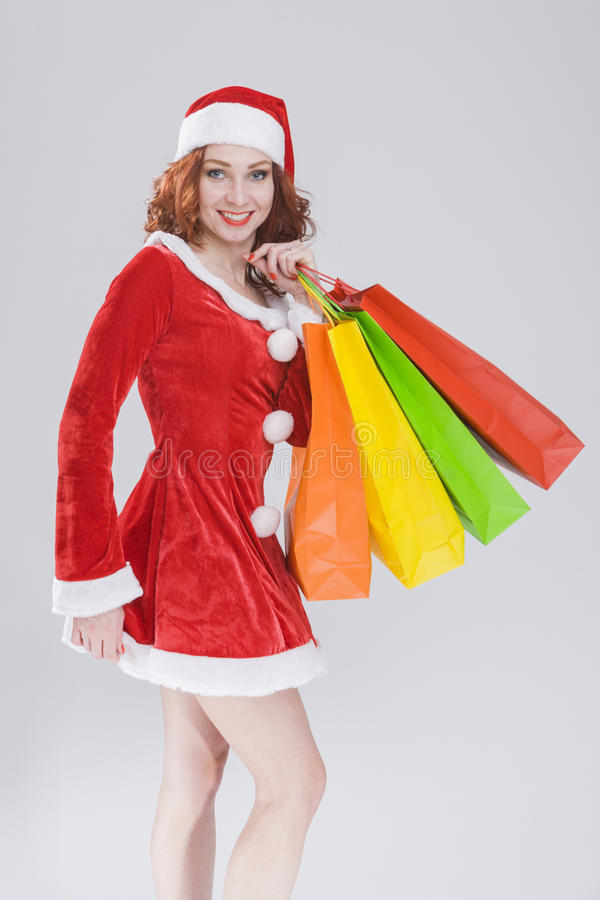 Christmas and New Year Concept and Ideas. Looking Young Caucasian Red Haired Female in Santa Hat Posing With Shopping Bags stock images