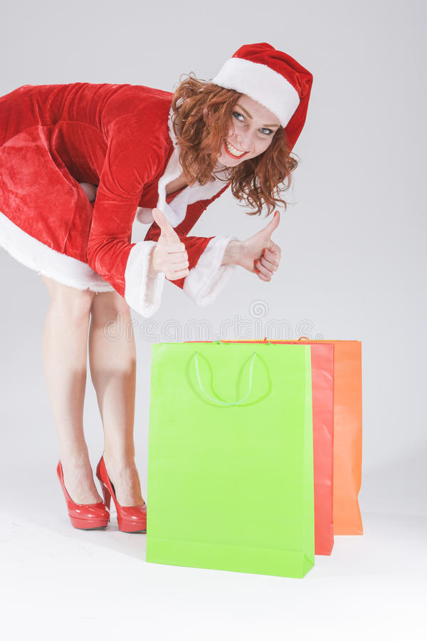 Christmas and New Year Concept and Ideas. Looking Young Caucasian Red Haired Female in Santa Hat Posing With Shopping Bags royalty free stock photos