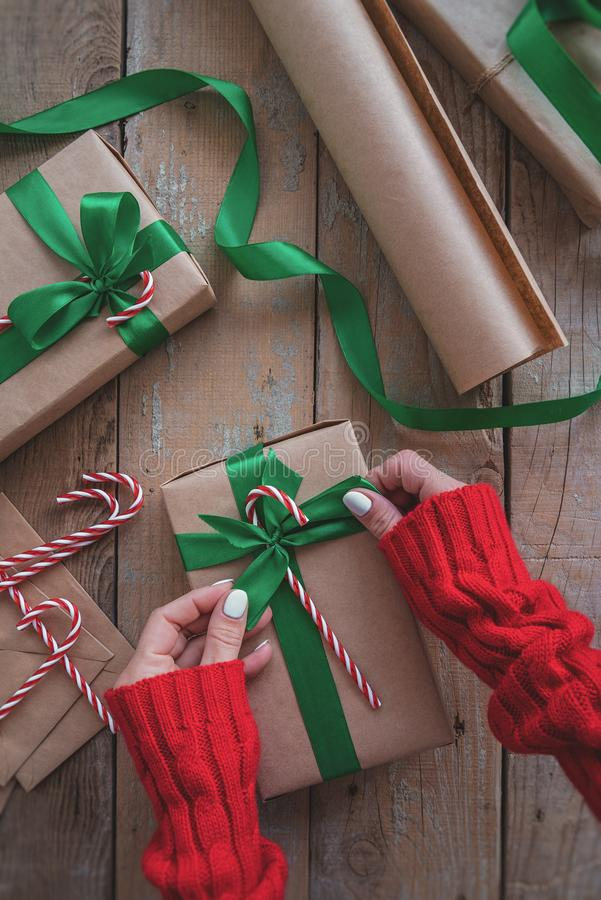 Woman hands holding a christmas present wrapped with craft paper, green ribbon and candy cane top view on wooden table royalty free stock photos