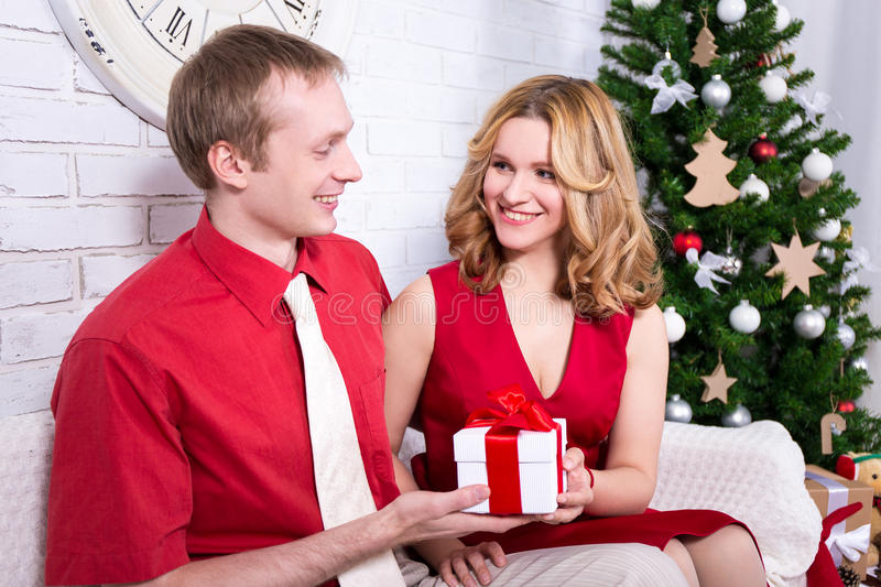Christmas and new year concept - young couple exchanging gifts royalty free stock photos