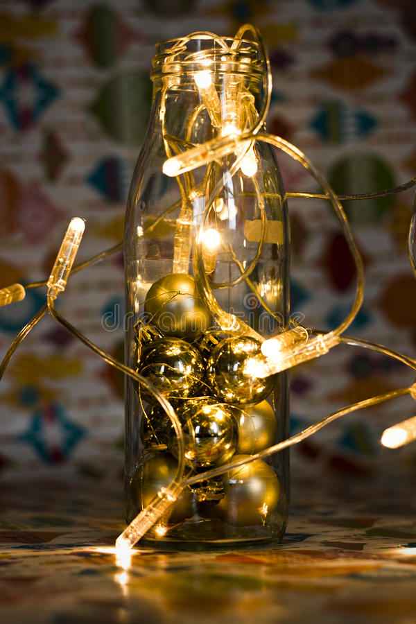 Christmas and new year decor with glass bottle and garland in vintage toning. royalty free stock image