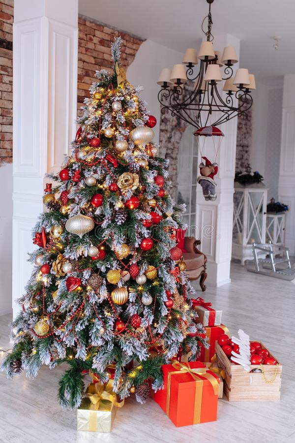 Christmas and New Year decorated interior room with red presents and New year tree in front of white wall. royalty free stock photo