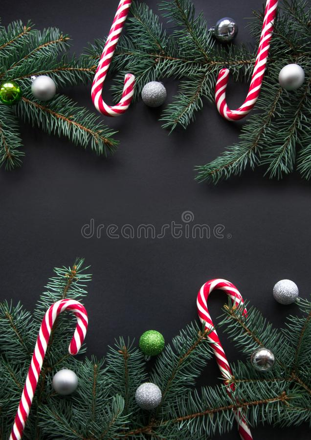 Christmas or New Year decoration background. Fir tree branches, spruce, candy, colorful balls on black background with copy space. stock photo