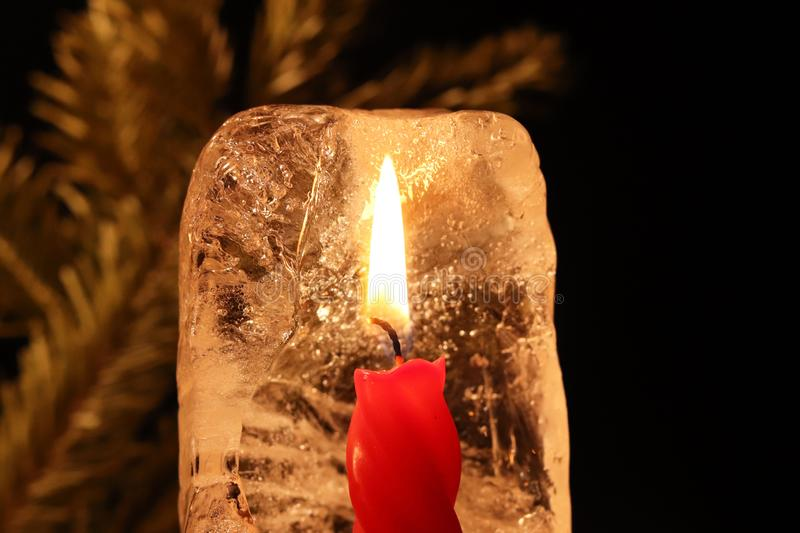 Christmas and New Year decoration. Burning red candle with ice on a dark background. Happy mood on a family holiday. Artistic royalty free stock image