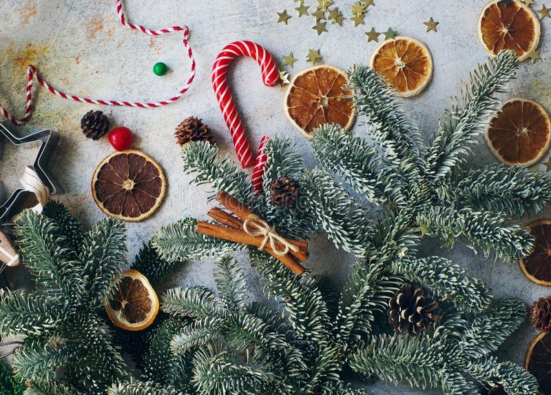 Christmas or New Year decoration, fir tree, candy cane, dry oranges, cones and cookie cutters royalty free stock photo