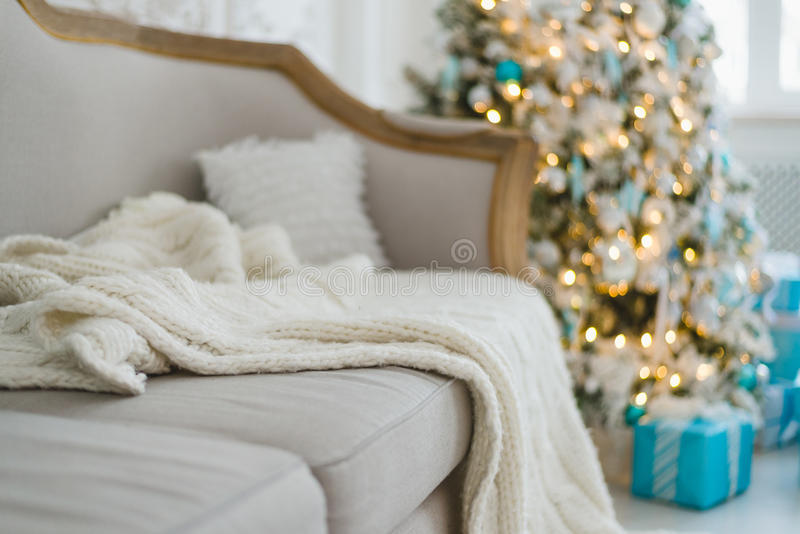 Christmas or new year decoration at Living room interior and holiday home decor concept. Calm image of blanket on a vintage sofa. With tree and gifts. Selective stock photos