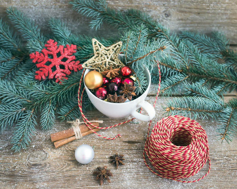 Christmas (New Year) decoration set: a cup full of colorful Christmas tree toys, cinnamon sticks and a decoration rope on royalty free stock photography