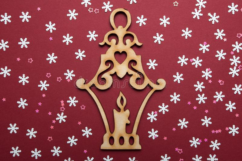Christmas and New Year decoration, wooden lantern with a candle inside with paper snowflakes on a red background stock image