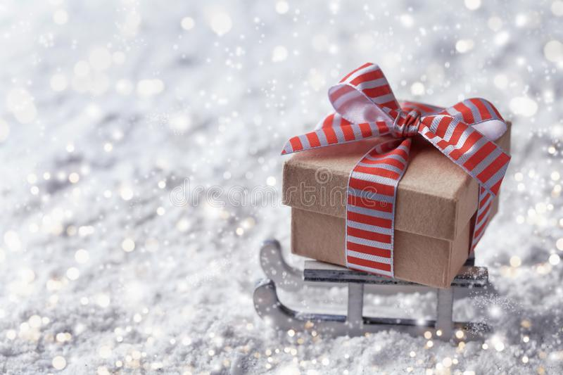 Christmas or New year delivery concept. Sleigh with a gift box in the snow royalty free stock photography