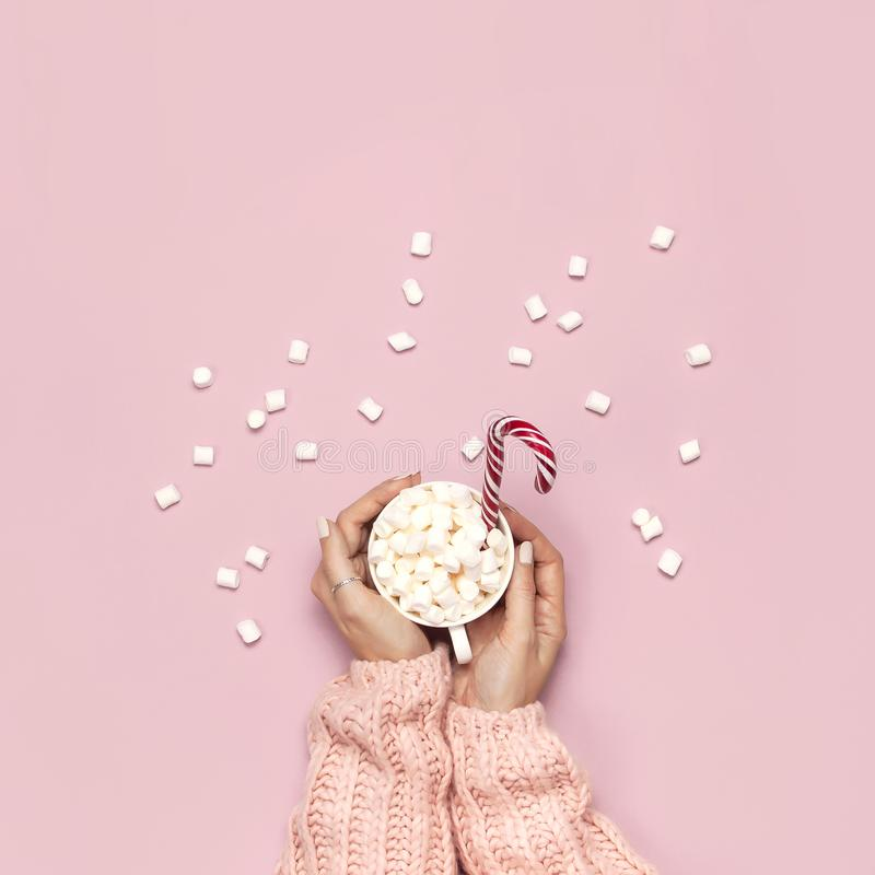 Christmas New Year drink, white mug with marshmallows in female hands in knitted sweater and Candy Cane on pink background top royalty free stock photography