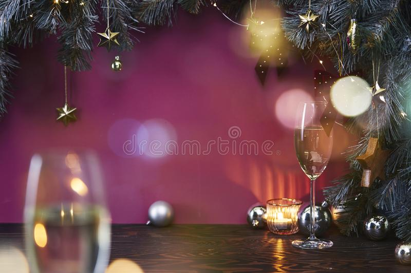 Christmas New Year eve mood with fir tree, champagne in glasses, decoration on dark wooden board, glare of light on background royalty free stock photo