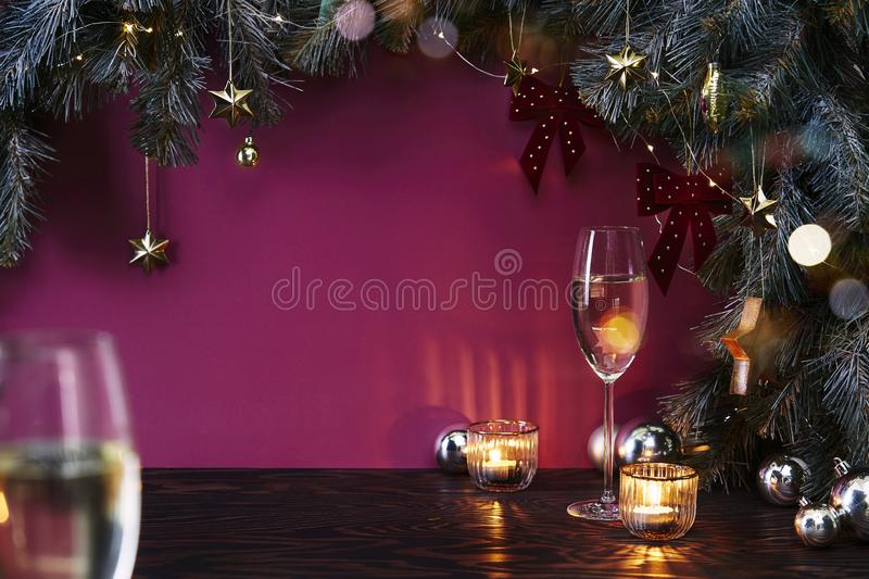 Christmas New Year eve mood with fir tree, champagne in glasses, decoration on dark wooden board, glare of light on background royalty free stock image