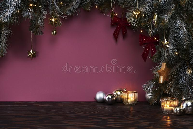 Christmas New Year eve mood with fir tree, decoration, balls on dark wooden board, violet background royalty free stock photo