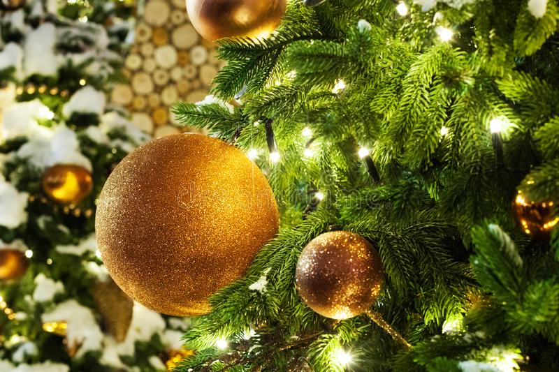 Christmas or New Year festive banner, golden christmas decorations glass balls, green pine branches, white snow and shiny lights stock photo