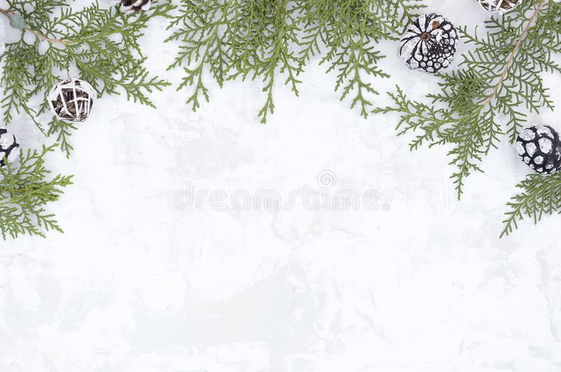 Christmas New Year flat lay frame made from pine cones and fir branches on white snow texture. Mockup with copy space stock image