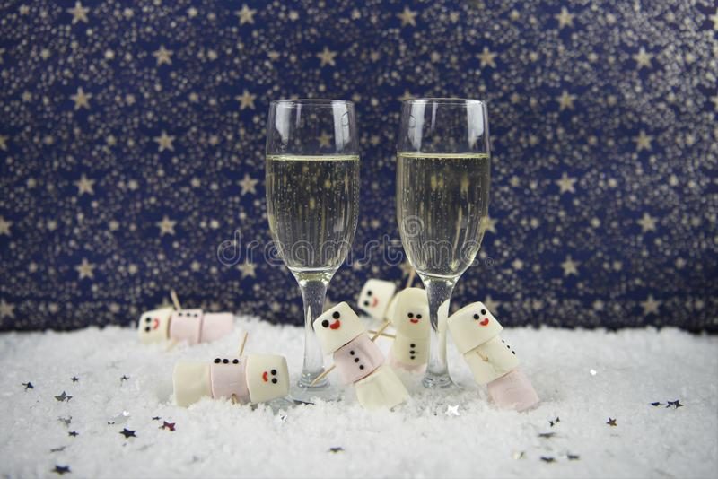 Christmas or New Year food and drink photography image using marshmallows shaped as snowman in snow with glasses of champagne stock photos
