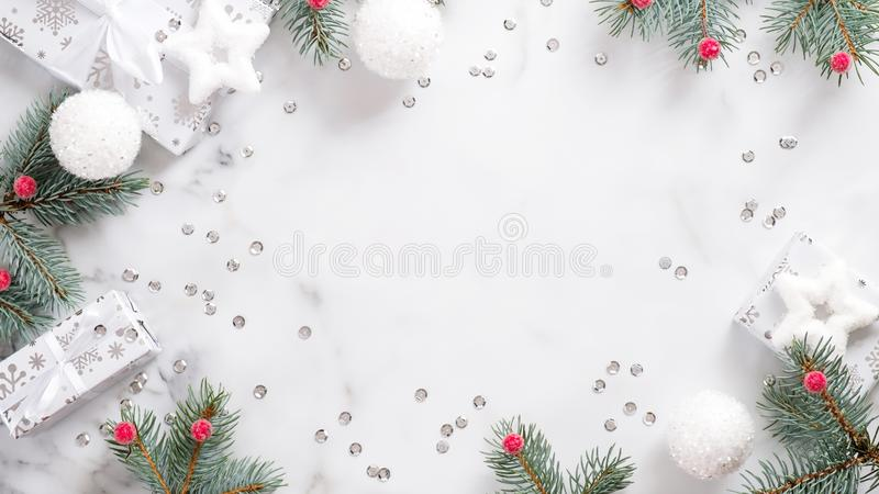 Christmas or New Year frame made of fir tree branch, white balls, gift boxes and confetti over marble background. Christmas wide. Banner mockup. Flat lay, top stock photos