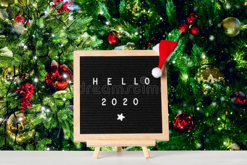 Christmas or new year frame or mockup for your project. Hello 2020 words on a letter board with santa hat against illuminated. Christmas trees background royalty free stock image