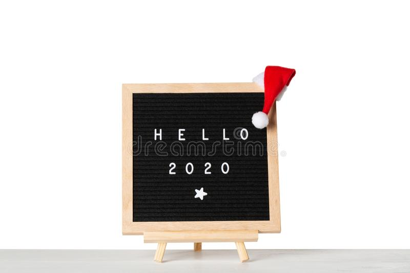 Christmas or new year frame or mockup for your project. Hello 2020 words on a letter board with santa hat against white isolated. Background stock images