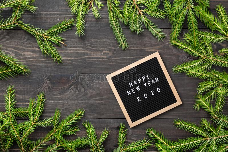Christmas or new year frame for your project. Happy new year 2020 words on a letter board with Christmas fir tree branches on a. Dark wooden board royalty free stock photography