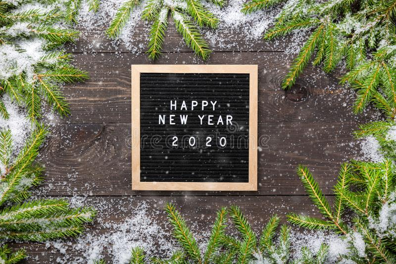 Christmas or new year frame for your project. Happy new year 2020 words on a letter board with Christmas fir tree branches and. Snow on a dark wooden board royalty free stock image