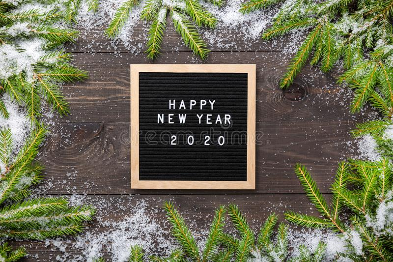 Christmas or new year frame for your project. Happy new year 2020 words on a letter board with Christmas fir tree branches and. Snow on a dark wooden board stock image