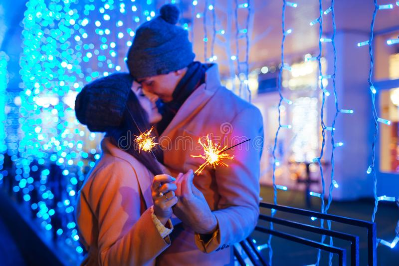 Christmas and New year fun concept. Couple in love burning sparklers by holiday illumination outdoors. Festive holidays stock image