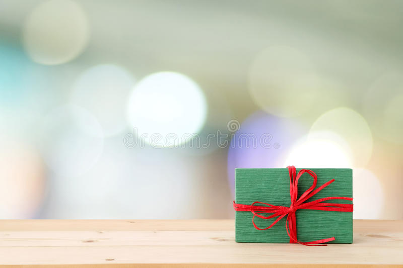 Christmas, new year gift box on wood table over blur festive bokeh light background, with copy space for greeting text, greeting royalty free stock photography