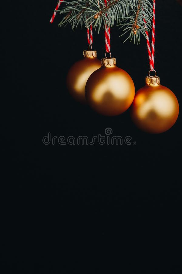Christmas and new year gift-card. branches of fir-tree and decoration with golden balls with red thread on a black background isol stock image
