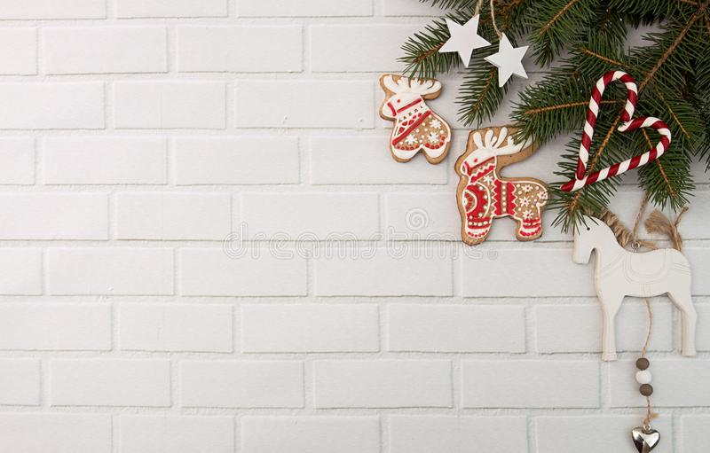 Christmas New Year holiday background. Decoration with red gingerbread cookies elk, deer, candy cane and fir branch tree against royalty free stock photography
