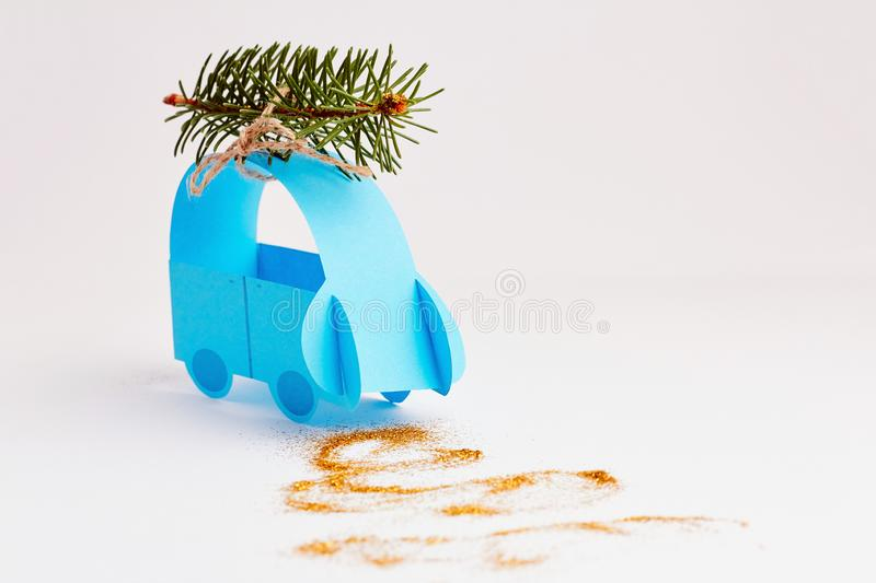 Christmas and New Year holiday card. Blue paper car with christmas tree over white background. Flat lay, top view with copy space stock photo