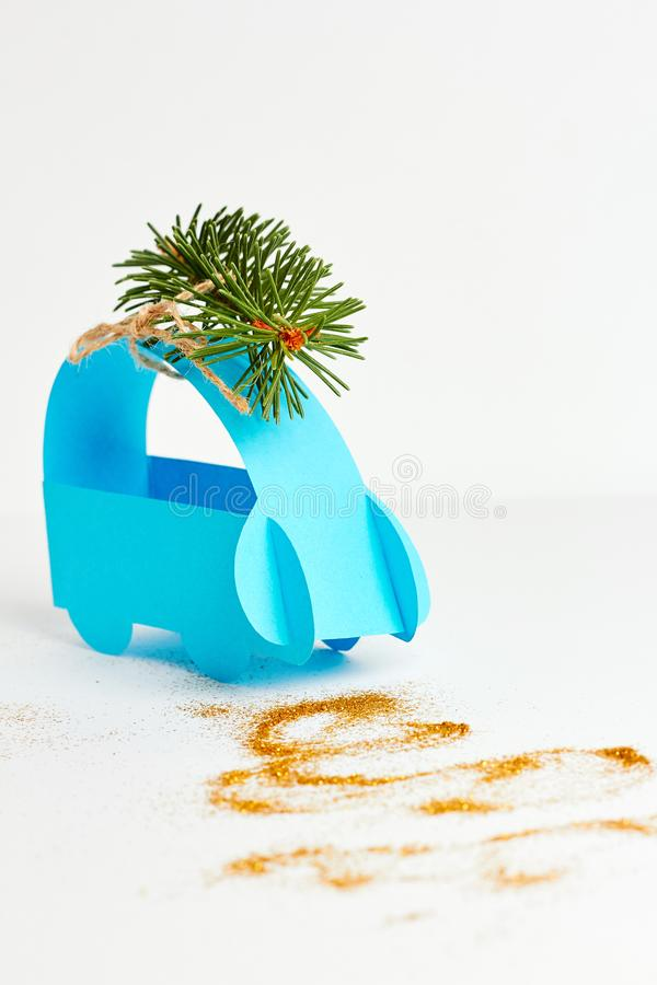 Christmas and New Year holiday card. Blue paper car with christmas tree over white background stock photos