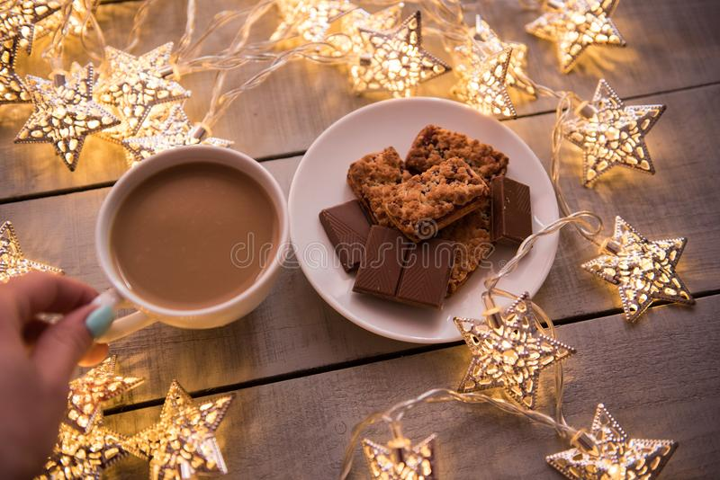 Christmas and new year holiday celebration concept background. Cup of coffee, homemade chocolate cookie and peanut biscuit, lighte stock photos