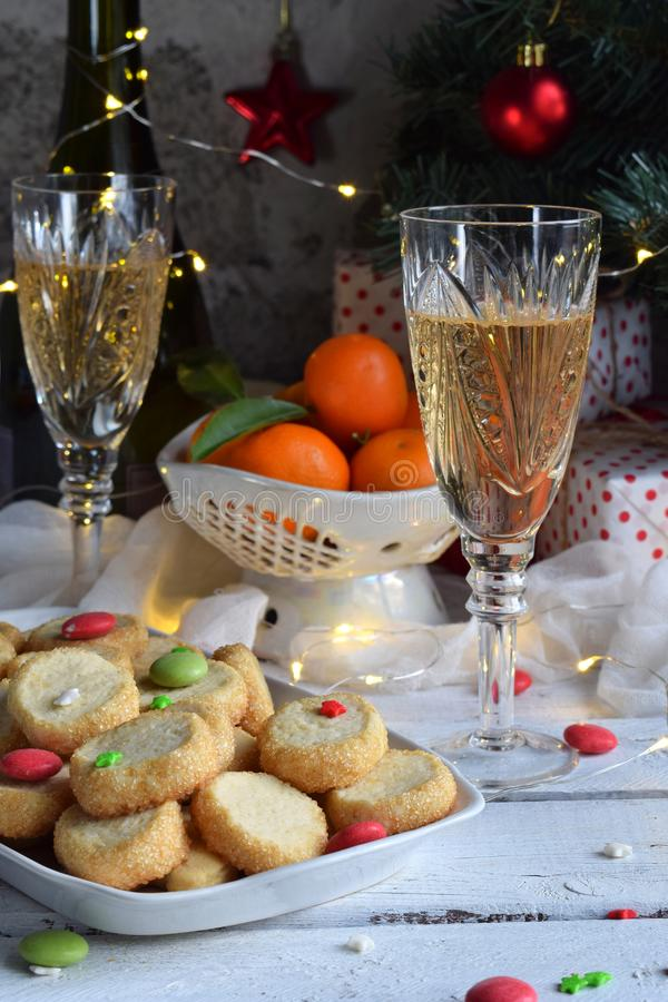 Christmas and new year holiday celebration concept background. Glass of champagne, tangerines, homemade cookies, xmas tree decorat stock image