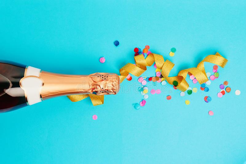 Christmas and New Year or holiday festive background. Bottle of champagne, golden ribbon and colored confetti over blue background. Flat lay, top view royalty free stock images