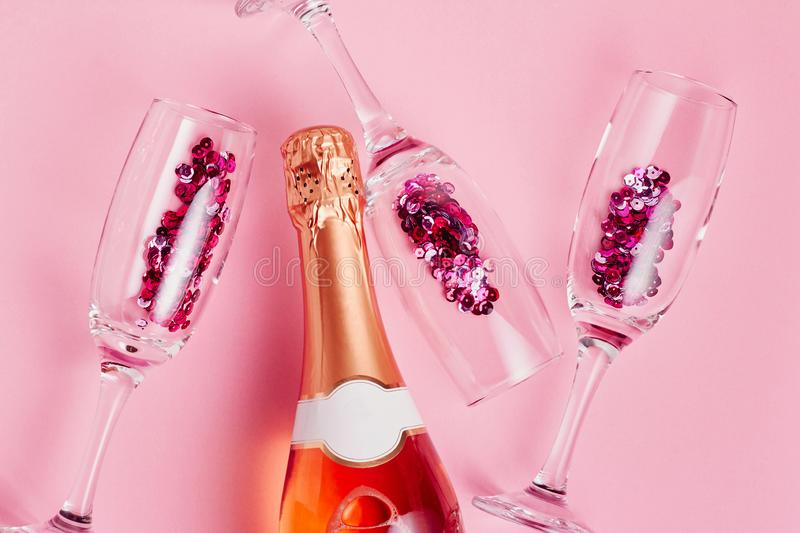 Christmas and New Year holiday festive card. Bottle of champagne and glasses with sparkles over pink background. Flat lay, top view stock image