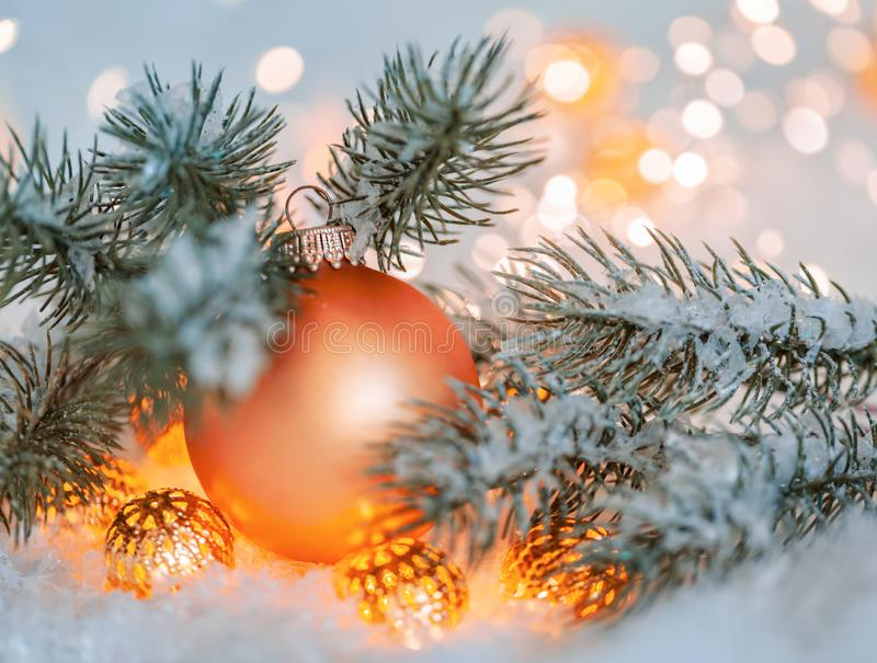 Holiday greeting card. Beautiful orange ball. Christmas and New Year Holiday greeting card. Beautiful orange ball, pine branches and a garland in the snow stock images