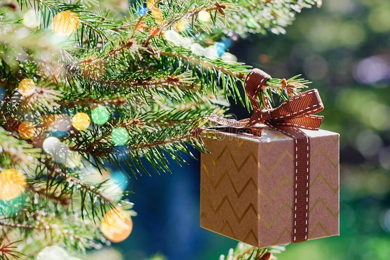 Christmas and New Year holidays card. Gift box hanging on Christmas tree branch on blue green background. Side view, selective focus royalty free stock photos