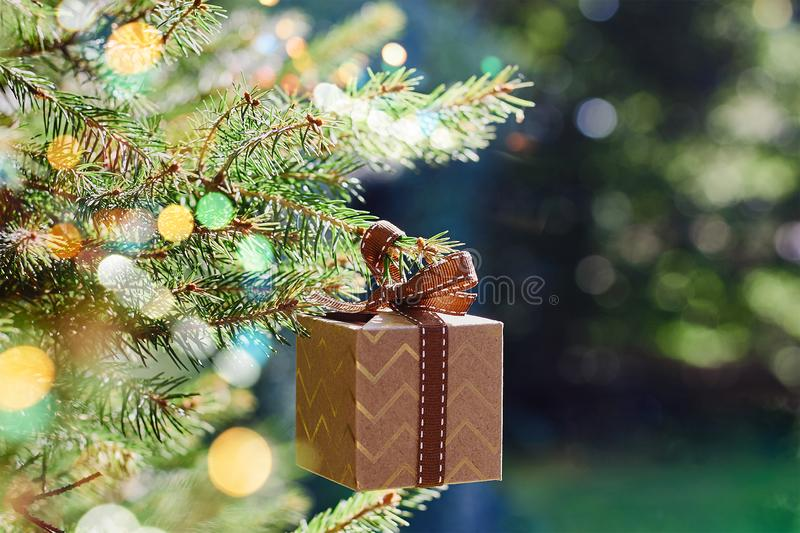 Christmas and New Year holidays card. Gift box hanging on Christmas tree branch on blue green background. Side view, selective focus royalty free stock photography
