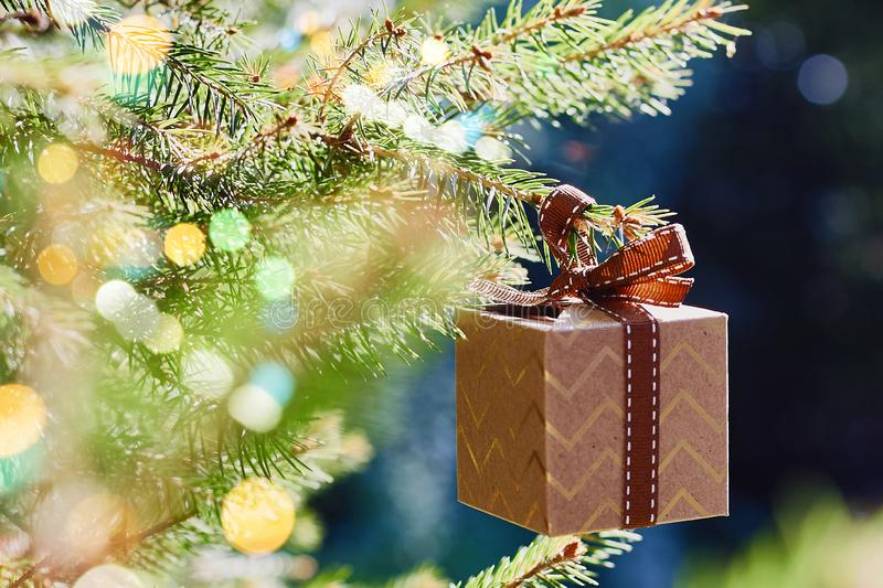 Christmas and New Year holidays card. Gift box hanging on Christmas tree branch on blue green background. Side view, selective focus stock images