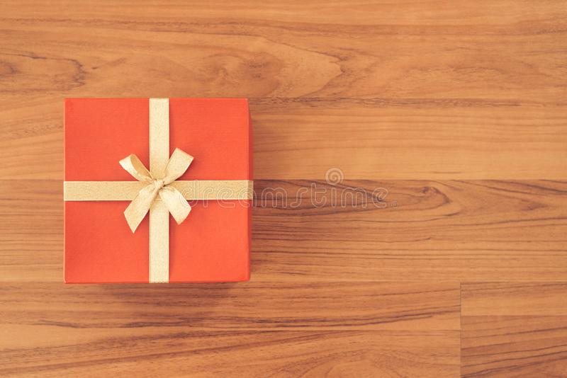 Christmas and New Year holidays gift box wrapped with red paper and yellow ribbon bow on wood table - top view on wooden table top. Background royalty free stock image