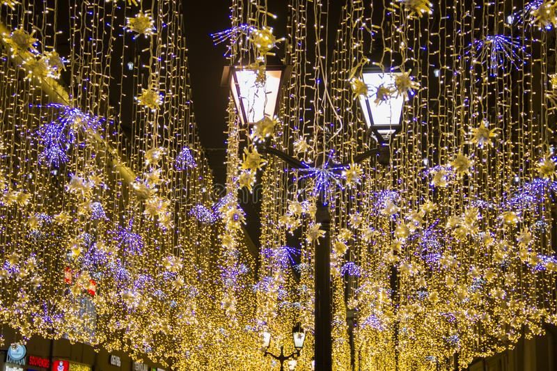 Christmas and New Year holidays illumination outdoor in city street at night. Golden shimmering and waving garlands with classical street lights royalty free stock photography